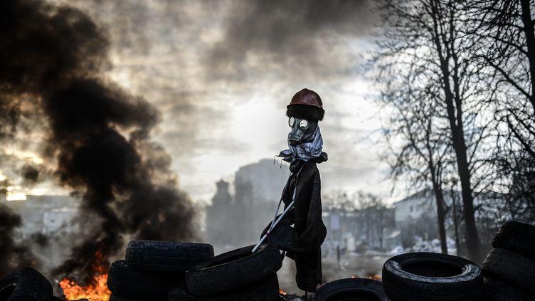 Un épouvantail fait d'oripeaux de manifestants au sommet d'une barricade, le 21 février 2014 à Kiev (Ukraine). (BULENT KILIC / AFP)