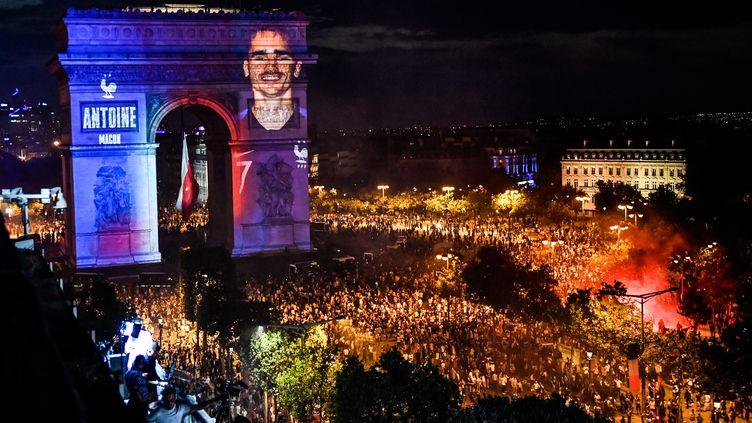 Devant une foule de supporters venus fêter la victoire des Bleus, avenue des Champs-Elysées à Paris, le visage d'Antoine Griezmann apparaît sur l'arc de Triomphe, le 15 juillet 2018, vingt ans après celui de Zinédine Zidane. (GERARD JULIEN / AFP)