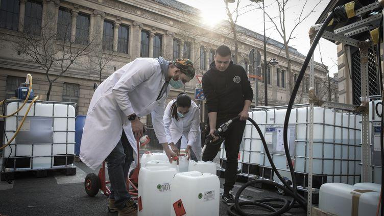 La pharmacie Delpech avait mis en place une chaîne de production de gelhydroalcoolique dans la rue, à Paris, le 27 mars 2020. (PHILIPPE DE POULPIQUET / MAXPPP)
