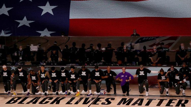 Des joueurs des Lakers et des Clippers posent un genou à terre, le 30 juillet 2020, en Floride. (MIKE EHRMANN / GETTY IMAGES NORTH AMERICA / AFP)