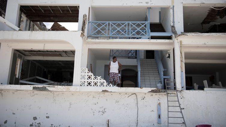 Une femme devant sa maison, détruite par l'ouragan Irma à Grand-Case, sur l'île de Saint-Martin, le 11 septembre 2017. (MARTIN BUREAU / AFP)