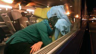 Un usager de la SNCF dort dans un train, en novembre 2008, dans un train bloqué en gare du Mans suite à un incident technique. (JEAN-FRANCOIS MONIER / AFP)