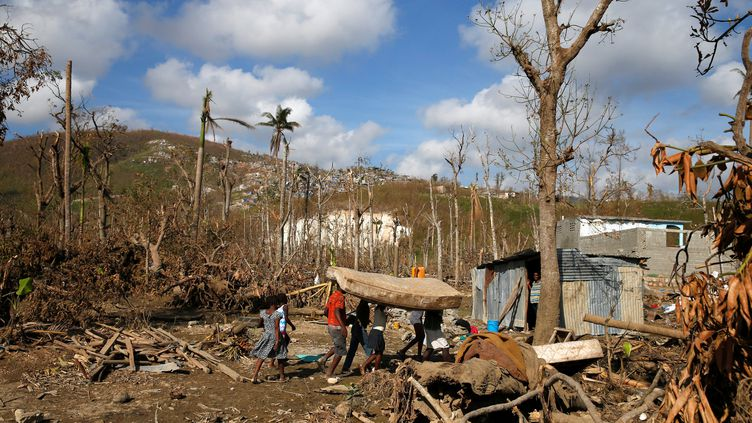 Des personnes portent un matelas après le passage de l'ouragan Matthew, en Haïti, le 13 octobre 2016. (CARLOS GARCIA RAWLINS / REUTERS)
