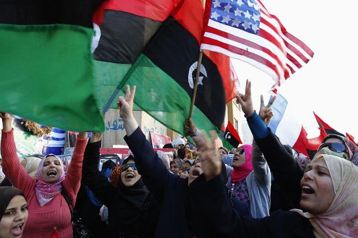 Des manifestants libyens brandissant côte à côte le nouveau drapeau de la Libye et celui des Etats-Unis, le 31 mars 2011 à Benghazi (Libye). ( YOUSSEF BOUDLAL / REUTERS)