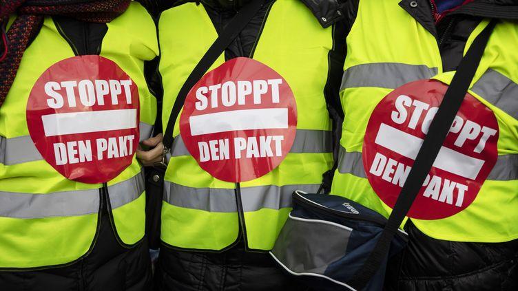 """Des personnes prenant part à une manifestation organisée par des groupes d'extrême droite contre la signature du pacte de l'ONU sur les migrations, et portant des """"gilets jaunes"""" en référence au mouvement français, le 1er décembre 2018 à Berlin (Allemagne). (CHRISTOPH SOEDER / DPA / AFP)"""