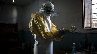 Un agent de santé met son équipement de protection avant d'entrer dans un centre de traitement contre Ebola dans le nord-est de la RDC en novembre 2018 (JOHN WESSELS / AFP)