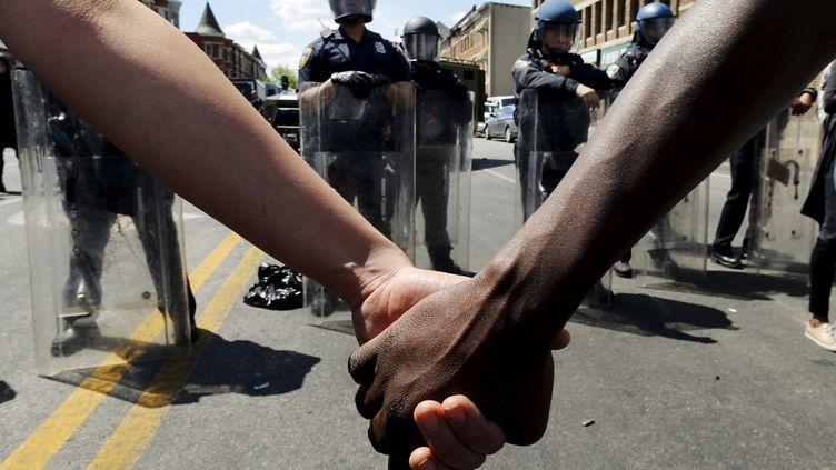 Les manifestations pacifiques de protestation se poursuivent à Baltimore pour protester contre la mort de Freddy Gray : ici, face à la police, des manifestants se tiennent la main, le 28 avril 2015. (© JIM BOURG / REUTERS / X90054)
