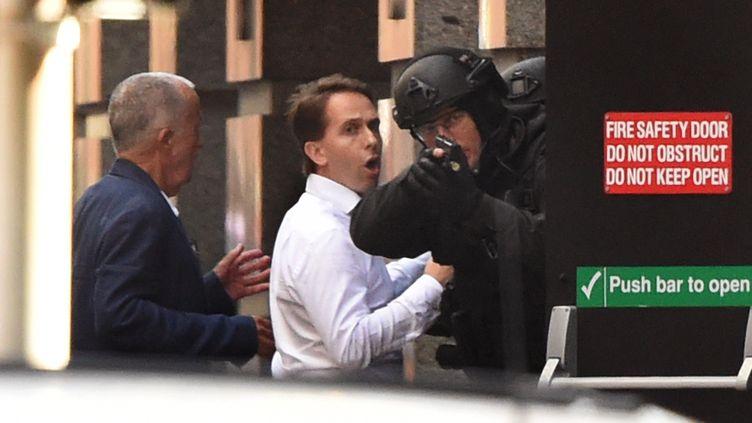 Deux otages se réfugient derrière un policier après s'être échappés d'un café du centre-ville de Sydney (Australie), où un homme armé retenait plusieurs personnes en otage, lundi 15 décembre 2014. (WILLIAM WEST / AFP)