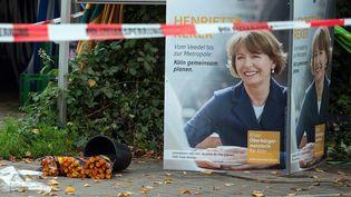 Des fleurs ont été déposées au pied d'une affiche de campagne de Henriette Reker près du lieu où elle a été agressée, à Cologne (Allemagne), le 17 octobre 2015. (FEDERICO GAMBARINI / DPA / AFP)