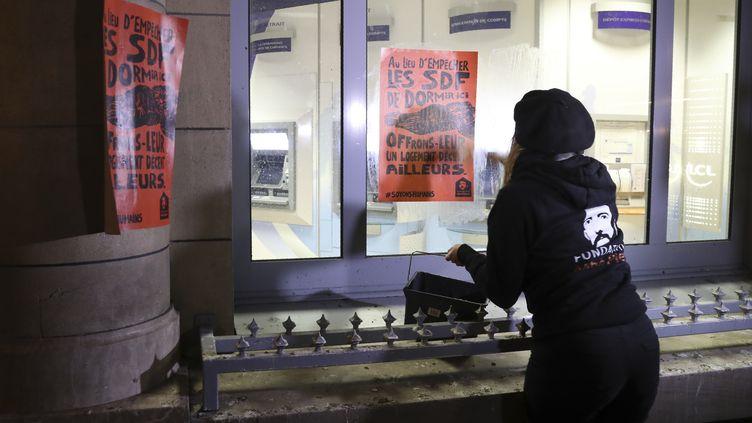 Une militante de la Fondation Abbé Pierre colle des affiches d'une campagne contre les dispositifs anti-sdf sur la façade d'une banque, le 6 décembre 2017 à Paris. (JACQUES DEMARTHON / AFP)