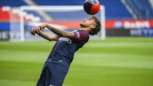 Le Parisien Neymar jongle sur la pelouse du Parc des Princes vendredi 4 août après sa présentation à la presse. (LIONEL BONAVENTURE / AFP)