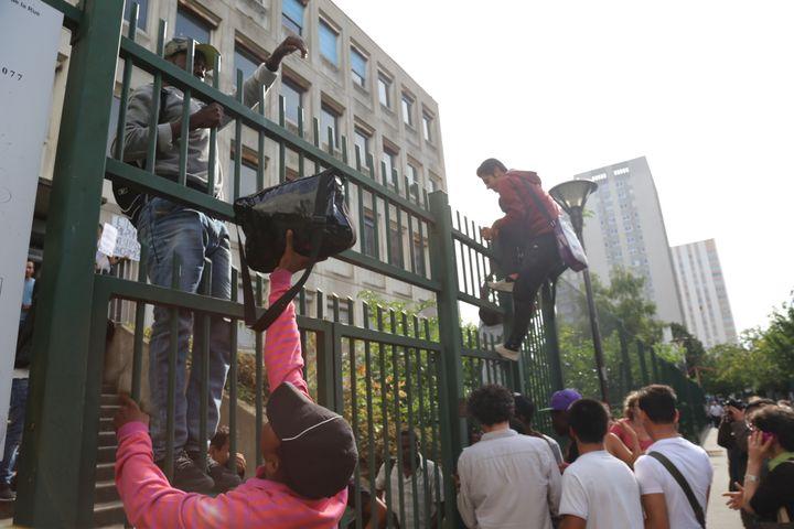 Des migrants escaladent la grille du lycée désaffecté Jean-Quarré, dans le 19e arrondissement de Paris, le 31 juillet 2015. (CITIZENSIDE/ANTHONY DEPERRAZ / CITIZENSIDE.COM)