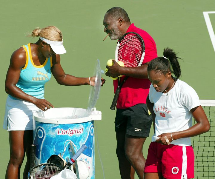 Serena Williams (à gauche) et Venus Willams (à droite) lors d'un entraînement avec leur père Richard Williams, en 2002, lors de l'US Open, à New York (Etats-Unis). (TIMOTHY A. CLARY / AFP)