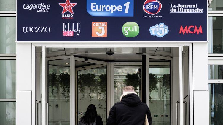 Deux personnes entrent dans le bâtiment du groupe Lagardère,à Paris, dans lequel se trouve la rédaction d'Europe 1. (PHILIPPE LOPEZ / AFP)