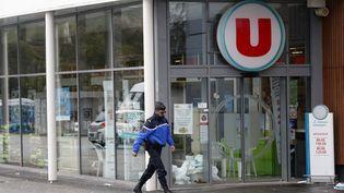 Un gendarme passe devant le Super U de Trèbes (Aude), samedi 24 mars 2018, au lendemain d'une prise d'otage menée par un terroriste jihadiste. (MAXPPP)