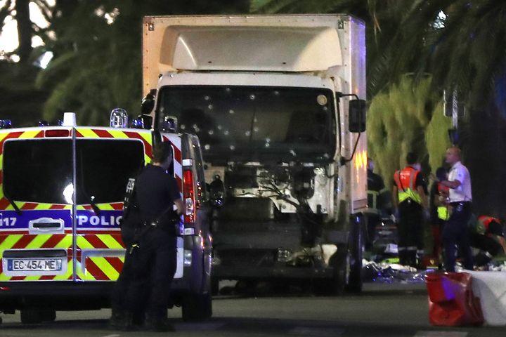 Des policiers près du camion blanc qui a foncé dans la foule sur la promenade des Anglais, à Nice (Alpes-Maritimes), le 14 juillet 2016. (VALERY HACHE / AFP)