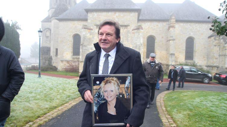 Jacky Kulik avec le portrait de sa fille, lors de la messe en sa mémoire, le 12 janvier 2014, àMonchy-Lagache (Somme). (FRED DOUCHET / MAXPPP)