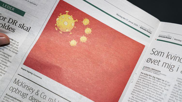 """Un dessin de presse publié le 27 janvier 2020 dans le journal danois """"Jyllands-Posten"""" représentant le drapeau chinois où les étoilesont été remplacées par des dessins de coronavirus. (IDA MARIE ODGAARD / RITZAU SCANPIX / AFP)"""