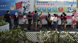 Des électeurs font la queue à l'occasion des primaires à Hong Kong, le 11 juillet 2020. (MAY JAMES / AFP)