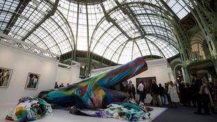 Katarina Grosse lors d'une résidence à la villa Medicis à Rome a récupéré des pins abattus, qui avaient été plantés il y a 200 ans par Ingres.Avec un pistolet à peinture, l'artiste allemande a transformé cette nature morte en bûcher coloré, présenté au Grand Palais, à Paris, le 17 octobre 2018. (THOMAS SAMSON / AFP)