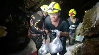 Des sauveteurs portent des vivres, le 5 juillet 2018, dans la grotte de Tham Luang, en Thaïlande, où treize personnes sont piégées depuis le 23 juin. (HANDOUT . / X80001)