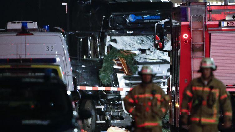 Des pompiers à proximité du camion qui a foncé sur un marché de Noël de Berlin (Allemagne), le 19 décembre 2016. (FABRIZIO BENSCH / REUTERS)