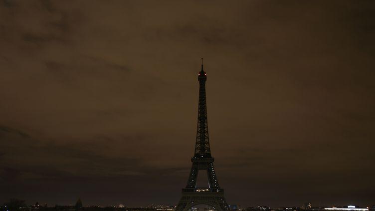 La tour Eiffel éteinte, le 22 mars, en hommage aux victimes de l'attentat terroriste survenu à Londres (Royaume-Uni), le 22 mars 2017. (ZAKARIA ABDELKAFI / AFP)