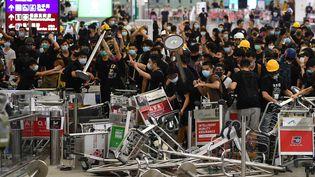 Des manifestants pro-démocratie ont, comme la veille, envahi l'aéroport d'Hong Kong, le mardi 13 août 2019. (MANAN VATSYAYANA / AFP)