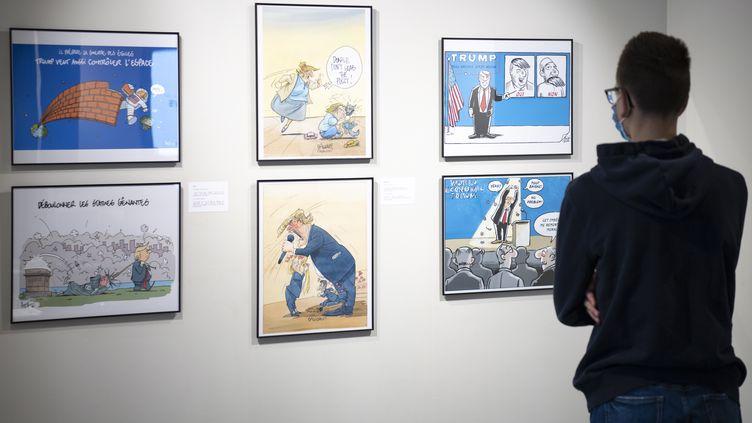 """Une personne regarde des caricatures représentant Donald Trump lors de la dernière préparation avant la nouvelle exposition """"Ça se dessine pour la Maison Blanche"""" à la Maison du dessin de presse, à Morges, en Suisse, le 24 octobre 2020. (LAURENT GILLIERON / EPA/ NEWSCOM / MAXPPP)"""