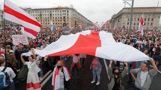 Des manifestants portent un drapeau de la contestation en Biélorussie, à Minsk, le 23 août 2020. (VASILY FEDOSENKO / REUTERS)