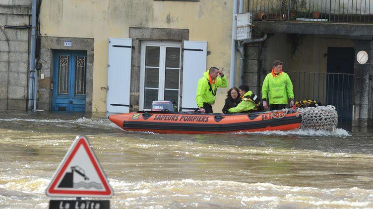 Des membres des secours viennent en aide à une habitante de Quimperlé (Finistère) alors que la ville est sous les eaux, le 7 février 2014. (FRANK PERRY / AFP)