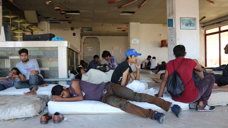 Des migrants se reposent devant l'ancienne réception de l'hôtel Captain Elias, le 19 août 2015 à Kos (Grèce). (BENOIT ZAGDOUN / FRANCETV INFO)