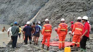 Des pompiers tentent de porter secours à des mineurs emportés par un glissement de terrain causé par la mousson, le 2 juillet 2020 àHpakant, en Birmanie. (HANDOUT / MYANMAR FIRE SERVICES DEPARTMENT / AFP)