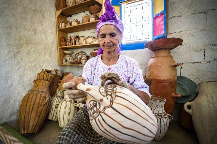 La potière marocaine Aicha Tabiz, également connue sous le nom de Mama Aicha, tient l'une de ses œuvres près du village d'Ourtzagh, au pied des montagnes du Rif, le 12 juin 2019. (FADEL SENNA / AFP)