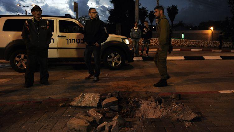 Des soldats israéliens et des civils se tiennent devant un cratère creusé par une roquette à Sderot, dans le sud d'Israël, le 12 mars 2014. (DAVID BUIMOVITCH / AFP)