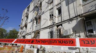 Un cordon de sécurité installé autour d'un immeuble détruit par une roquette palestinienne, dans la ville israélienne d'Ashkelon, près de la bande de Gaza. (JACK GUEZ / AFP)