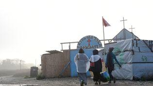 """Des migrants marchent devant une église, dans la """"jungle"""" de Calais (Pas-de-Calais), dimanche 23 octobre. (FRANCOIS LO PRESTI / AFP)"""