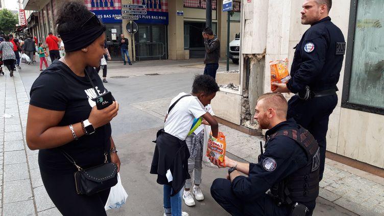 Les policiersdistribuent des bonbons dans les rues de Saint-Denis (NATHALIE REVENU / MAXPPP)