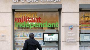 Un passant regarde l'une des vitres des locaux de l'association de consommateurs UFC-Que Choisirà Paris. (JACQUES DEMARTHON / AFP)