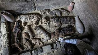 Nécropole de Saqqara : des archéologues nettoient des momies de chats dans une des tombes découvertes.  (KHALED DESOUKI / AFP)