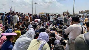 Des Afghans le long d'une route en attendant de monter à bord d'un avion militaire américain pour quitter le pays,àl'aéroport militaire de Kaboul, le 20 août 2021. (WAKIL KOHSAR / AFP)