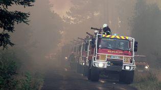 Une colonne de camions de pompiers se forme au bord d'une route, le vendredi 24 juillet. Les lances à incendie sont prêtes à asperger d'eau le sol brûlant. Près de 400 pompiers luttent sans relâche contre les flammes. (TARIS PHILIPPE / MAXPPP)