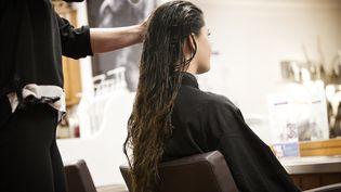 Une femme se fait coiffer dans un salon. Photo d'illustration. (AMELIE-BENOIST / BSIP)