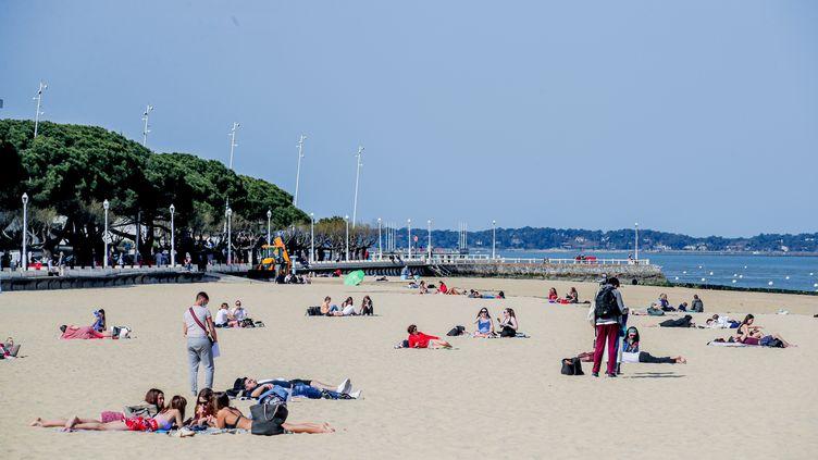 Des habitants profitent de la douceur des températures à Arcachon (Gironde), le 30 mars 2021. (GUILLAUME BONNAUD / MAXPPP)