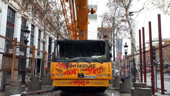 Une grue de chantier vandalisée et calcinée lors des heurts qui se sont produits sur les Champs-Elysées samedi 24 novembre. (BENJAMIN ILLY / FRANCE INFO)