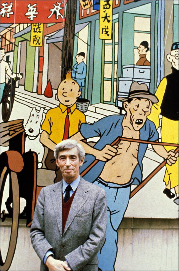 """Hergé pose devant un agrandissement d'une des cases de son album """"Le Lotus Bleu"""" à Bruxelles, en novembre 1979. (MARC GANTIER / GAMMA-RAPHO)"""
