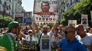 Portrait de Karim Tabbou brandi par les manifestants lors d'un rassemblement dans les rues d'Alger, le 27 septembre 2019, au lendemain de son arrestation. Karim Tabbou est devenu l'un des principaux visages du Hirak, le mouvement de contestation algérien. (RYAD KRAMDI / AFP)