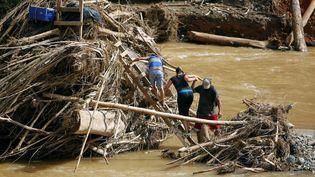 Après le passage d'un ouragan en octobre 2017, des personnes marchent parmi des débris pour accéder à une rivière à Porto Rico. (RICARDO ARDUENGO / AFP)