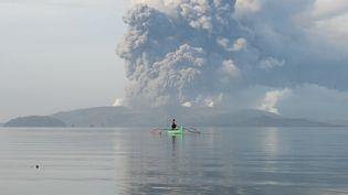Un homme navigue sur un canoë, non loin duvolcan Taal en éruption aux Philippines, le 13 janvier 2020. (TED ALJIBE / AFP)