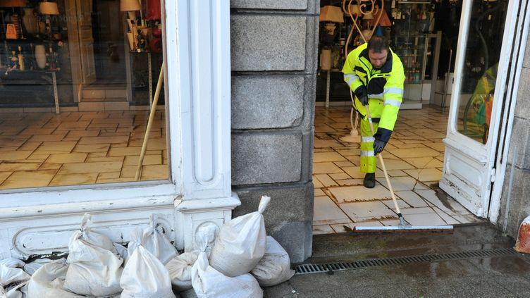 Un employé municipal nettoie un magasin de lampes inondé, le 7 février 2014 à Morlaix (Finistère). (MAXPPP)